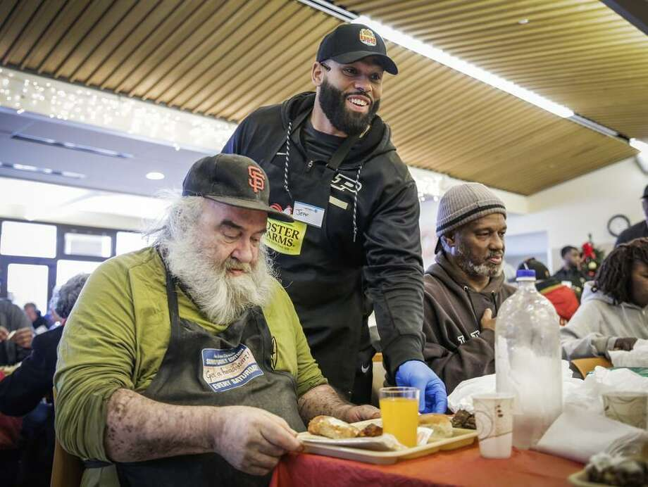 Purdue strength and conditioning coach Jeff Eaton (center) serves Joseph Folger lunch at St. Anthony Dining Room. Photo: Gabrielle Lurie / Gabrielle Lurie / The Chronicle / ONLINE_YES