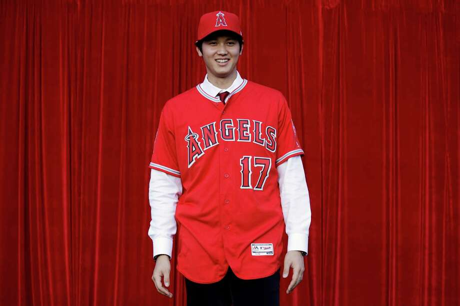 Baseball player Shohei Ohtani, of Japan, poses for photos after a news conference at Angel Stadium, Saturday, Dec. 9, 2017, in Anaheim, Calif. Ohtani, who intends to be both a starting pitcher and an everyday power hitter, turned down interest from every other big-league club to join two-time MVP Mike Trout and slugger Albert Pujols with the Angels, who are coming off their second consecutive losing season and haven't won a playoff game since 2009. (AP Photo/Jae C. Hong) ORG XMIT: ANS118 Photo: Jae C. Hong / Copyright 2017 The Associated Press. All rights reserved.