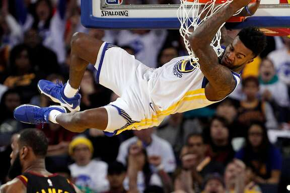 Jordan Bell (2) hangs on the rim on a dunk in the second half as the Golden State Warriors played the Cleveland Cavaliers at Oracle Arena in Oakland, Calif., on Monday, December 25, 2017.