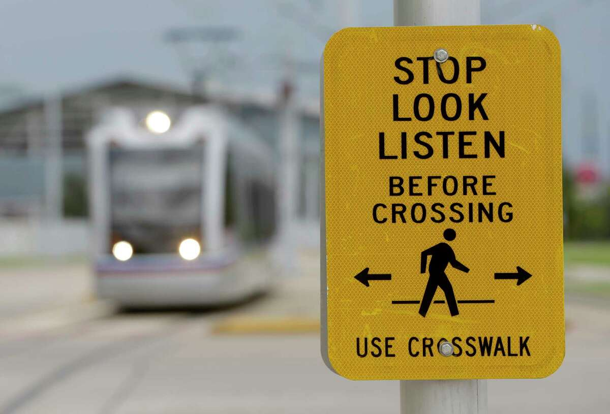 A crosswalk sign is posted near the Metro light rail station platform along the purple line at the Elgin/Third Ward station on July 11. The sign was part of early efforts to increase safety along the light rail tracks.