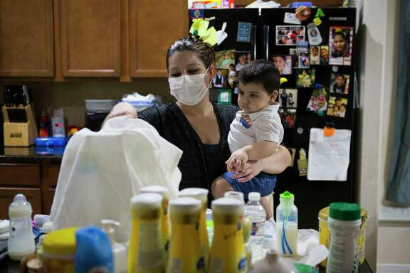 Blanca Romero prepares a bottle for her son Sebastian at home in Katy. Sebastian, who was born without a functioning immune system, received a stem cell transplant from his mother that should help him build cells that will fight infections.