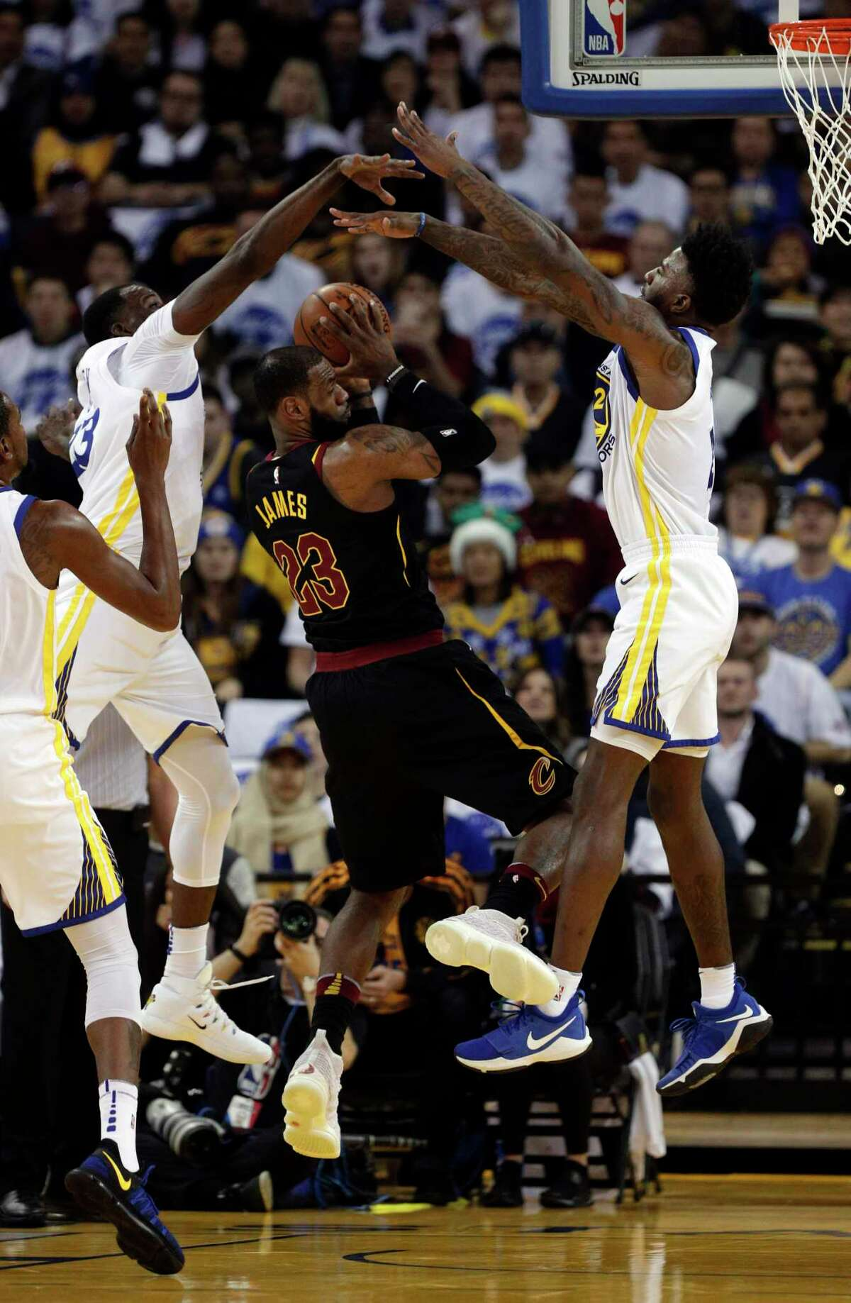 The Warriors' Draymond Green, left, and Jordan Bell put the squeeze on the Cavaliers' LeBron James.