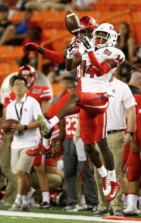 Fresno State defensive back Jaron Bryant, right, grabs an interception in front of UH receiver Steven Dunbar before returning it 44 yards for a fourth-quarter touchdown that gave the Bulldogs an insurmountable lead in Sunday's game. Photo: Jamm Aquino, MBR / © Honolulu Star-Advertiser 2017. All rights reserved.
