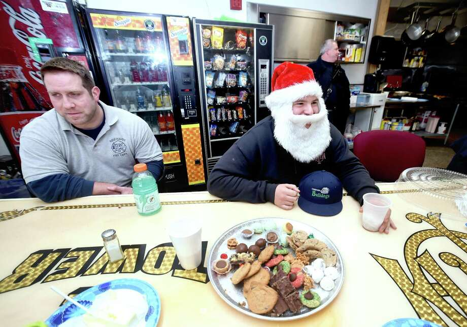 Firefighter Mark Misbach, right, dons a Santa Claus hat and beard during lunch at the New Haven Fire Department Headquarters on Christmas Day. At left is Lt. Patrick Grant. Photo: Arnold Gold / Hearst Connecticut Media / New Haven Register