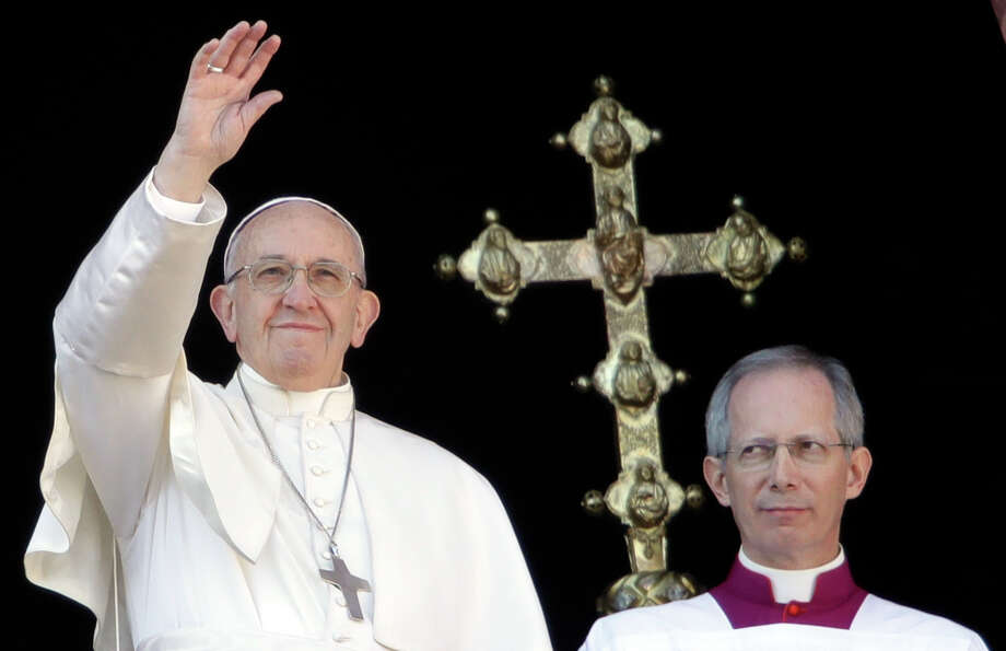 Pope Francis, flanked by Master of Ceremonies Bishop Guido Marini, waves to faithful during the Urbi et Orbi (Latin for ' to the city and to the world' ) Christmas' day blessing from the main balcony of St. Peter's Basilica at the Vatican, Monday, Dec. 25, 2017. (AP Photo/Alessandra Tarantino) Photo: Alessandra Tarantino / Copyright 2017 The Associated Press. All rights reserved.