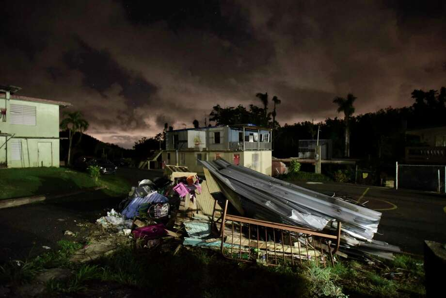 A mountain of rubble remains in front of a home in Morovis, Puerto Rico. By 4 p.m., some generators in the neighborhood start rumbling to life as darkness approaches.