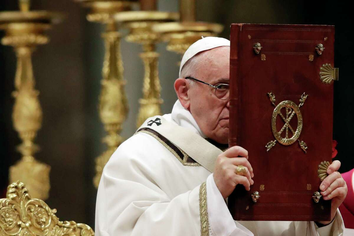 Pope Francis holds the book of the Gospel as he celebrates the Christmas Eve Mass in St. Peter's Basilica at the Vatican, Sunday, Dec. 24, 2017. (AP Photo/Alessandra Tarantino)