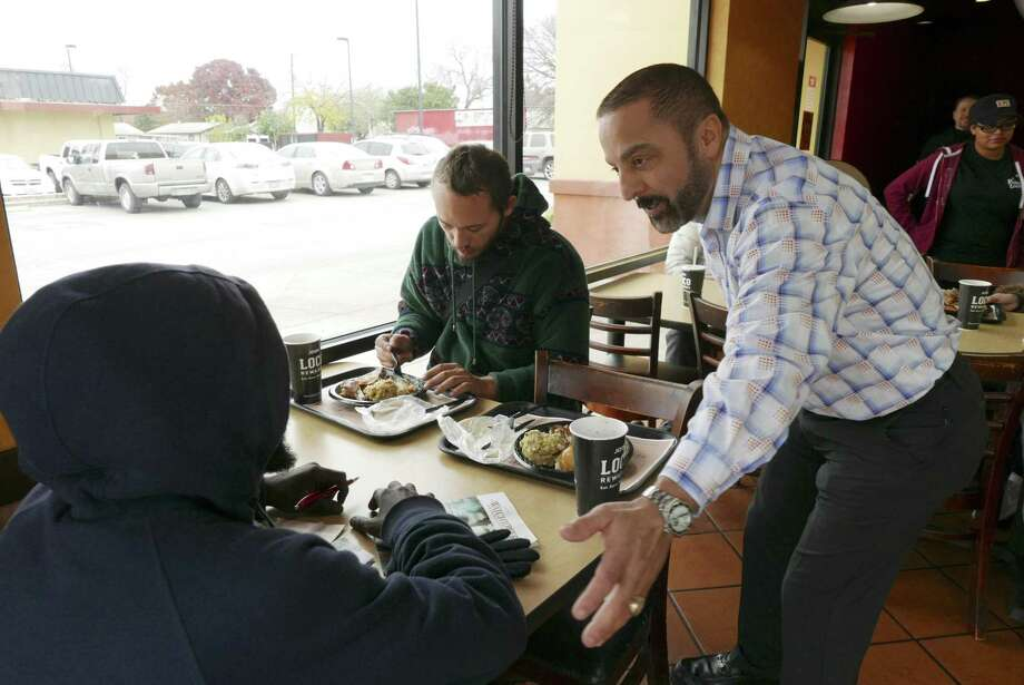 Atour Eyvazian, right, owner of El Pollo Loco restaurants, speaks with Nathaniel Harris, left, and and Phillip Jarrett at the 4645 W. Commerce St. location on Christmas Day, Monday, Dec. 25, 2017. Eyvazian opened this restaurant to the homeless for Christmas dinner. Photo: Billy Calzada, Staff / San Antonio Express-News