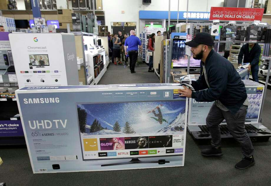 FILE - In this Thursday, Nov. 23, 2017, file photo, Jesus Reyes pushes a television down an aisle as he shops at a Black Friday sale at a Best Buy store in Overland Park, Kan. Shoppers feeling good about the economy, who are spending more than expected on items like kitchen gadgets, toys and coats, could make this the best holiday season in several years. (AP Photo/Charlie Riedel, File) Photo: Charlie Riedel / Copyright 2017 The Associated Press. All rights reserved.