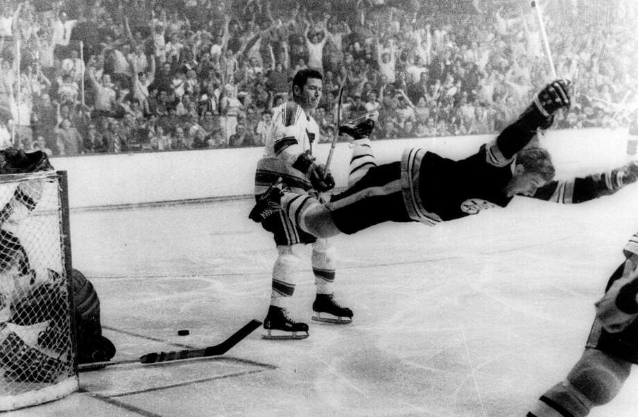 """FILE - In this May 10, 1970, file photo, Boston Bruins' Bobby Orr goes into the air after scoring a goal against the St. Louis Blues that won the Stanley Cup for the Bruins in Boston. As the NHL celebrates its 100th anniversary, Orr's goal is so important that it reached the finals of the """"Greatest Moments"""" bracket 47 years after it happened. (Ray Lussier/The Boston Herald via AP, File) Photo: Ray Lussier / AP1970"""