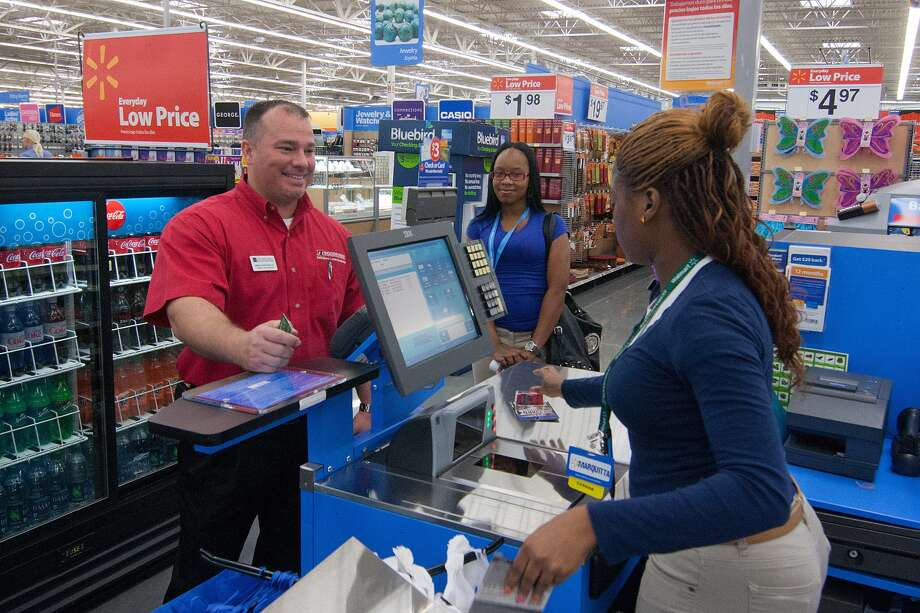 Marquitta Rhem helps customer Brian Kolenda II check out at the Heights Walmart. Seventy-three percent of cashiers are women, and those jobs have been identified as among the first to be affected by automation. Photo: R. Clayton McKee, Freelance / © R. Clayton McKee