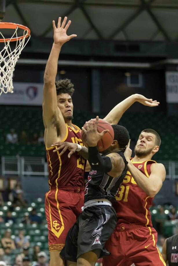 New Mexico State guard A.J. Harris, center, finds himself double teamed by Southern California forward Bennie Boatwright, left, and his teammate forward Nick Rakocevic, right, during the second half of an NCAA college basketball game at the Diamond Head Classic, Monday, Dec. 25, 2017, in Honolulu. Southern California defeated New Mexico State 77-72. (AP Photo/Eugene Tanner) Photo: Eugene Tanner / Associated Press