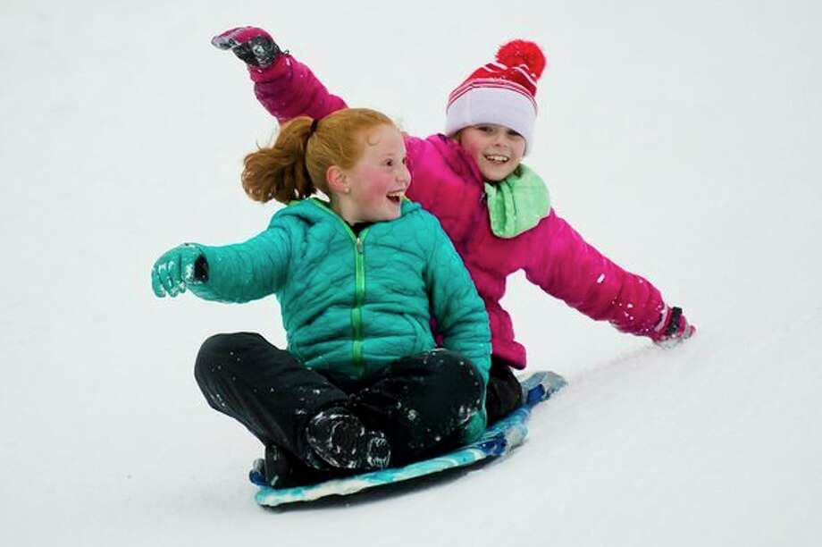 Pinconning residents Kaylee Doak, 9, right, and Sarah Yaros, 9, left, slide down the sledding hill at Midland City Forest on Friday. (Katy Kildee/kkildee@mdn.net)
