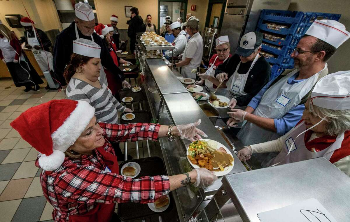 Volunteers get plates of food for the distribution to those in need during the Christmas Dinner at the Albany Rescue Mission Monday Dec 25, 2017 in Albany, N.Y. (Skip Dickstein/ Times Union)