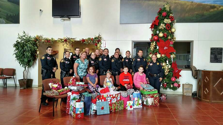 Laredo police officers pose for a photo with some of the children who received gifts through LPD's Blue Santa program. Photo: Courtesy