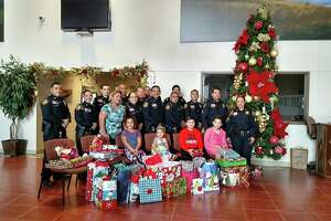 Laredo police officers pose for a photo with some of the children who received gifts through LPD's Blue Santa program.