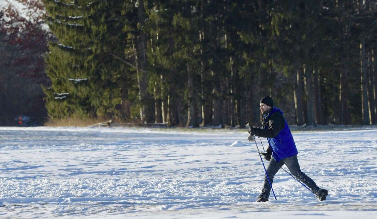 Cross-country skiers at Albany's Capital Hills golf course warm up on a bone-chilling day Tuesday.