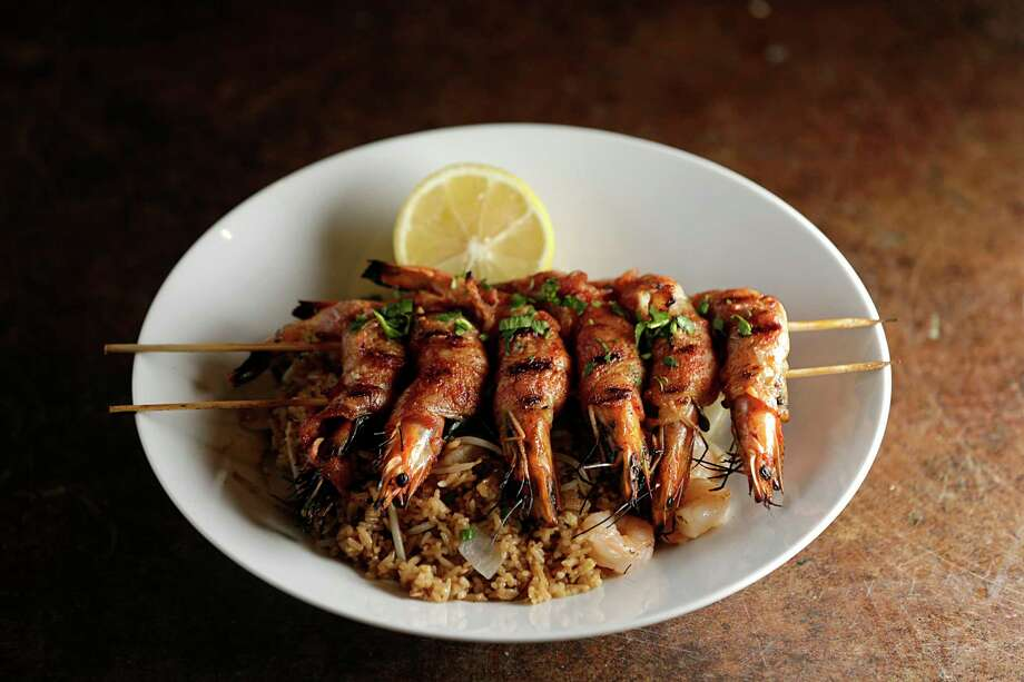 The Trung Sisters, shrimp wrapped with Thai basil, onions and bacon served over shrimp fried rice topped with lemon butter at Maba Pan-Asian Diner. Photo: James Nielsen, Staff / © 2016  Houston Chronicle