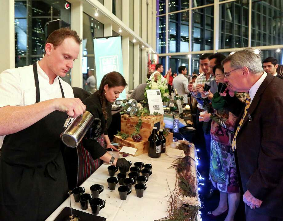 Austin Simmons, executive chef at Cureight, left, pours oyster caviar, fresh truffle and truffle potage, for guests at Truffle Masters 2017. The 2018 Truffle Masters event will be held on Jan. 29 at the Astorian. Photo: Jon Shapley, Staff / © 2017  Houston Chronicle