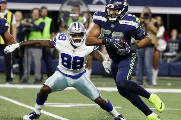 Dallas Cowboys wide receiver Dez Bryant (88) defends as Seattle Seahawks linebacker K.J. Wright (50) intercepts a pass intended for Bryant in the second half of an NFL football game, Sunday, Dec. 24, 2017, in Arlington, Texas. (AP Photo/Michael Ainsworth)