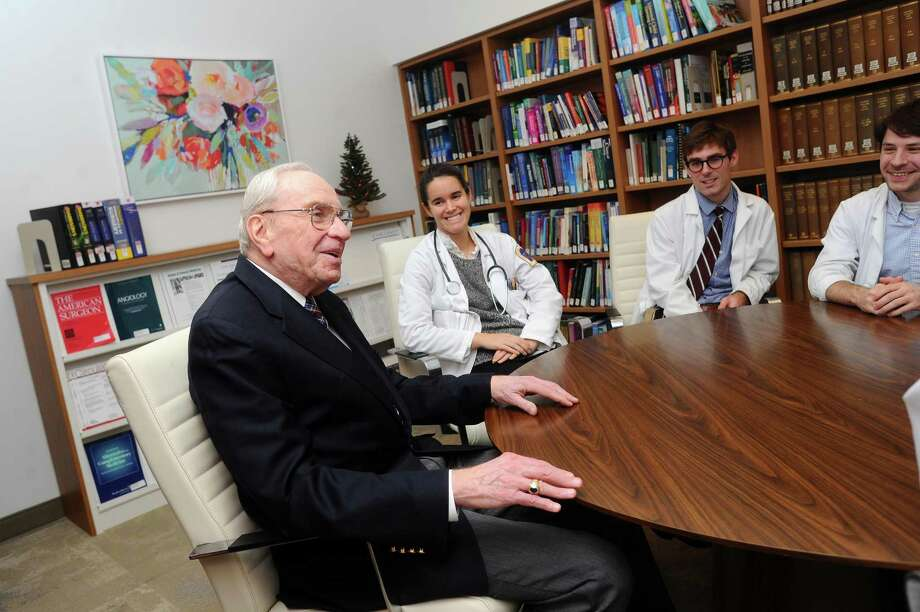 Dr. Noel Robin, chairman of the Department of Medicine at Stamford Hospital and a dean at Columbia University's College of Physicians and Surgeons, chats with medical students, from right, Aaron Kaplan, Nathan Danielson and Diana Stern, inside the library of the new Stamford Hospital in Stamford, Conn. on Tuesday, Dec. 19, 2017. Dr. Robin is retiring as the chairman at the end of the year but will continue to teach and see patients in the Stamford Hospital clinic. Photo: Michael Cummo / Hearst Connecticut Media / Stamford Advocate