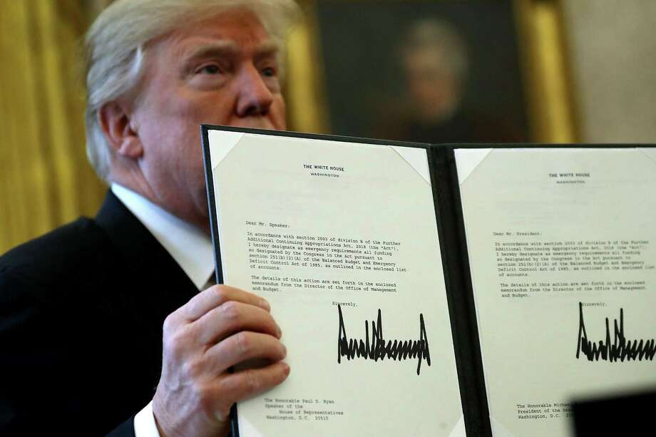 President Donald Trump holds up a copy of legislation he signed before  signing the tax reform bill into law in the Oval Office on Friday. Trump praised Republican leaders in Congress for all their work on the biggest tax overhaul in decades. Photo: Chip Somodevilla, Staff / 2017 Getty Images
