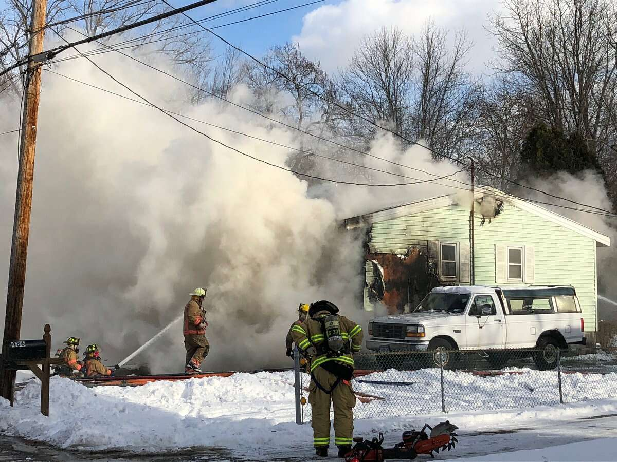 Guilderland firefighters fight the flames Tuesday at a home on Church Road in Guilderland.