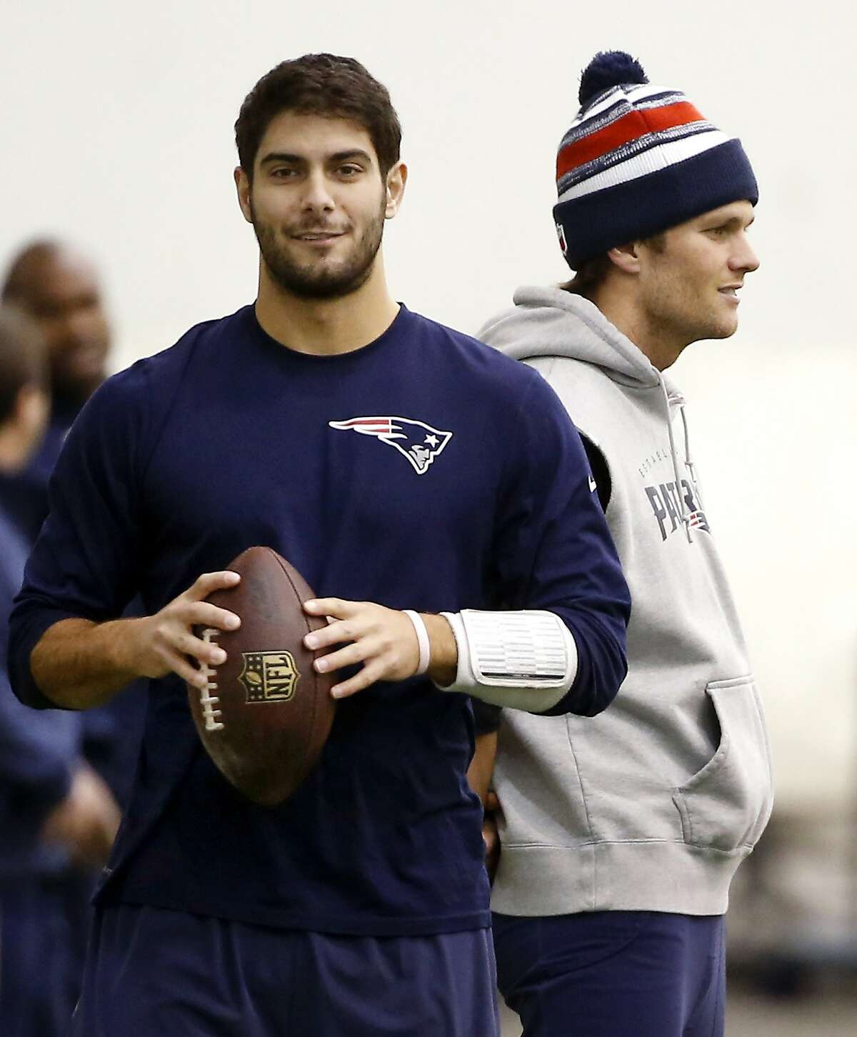 FILE- In this Feb. 1, 2015, file photo, New England Patriots backup quarterback Jimmy Garoppolo, left, holds a football as starting quarterback Tom Brady, right, stands by during a walkthrough at the NFL football team's facility in Foxborough, Mass.
