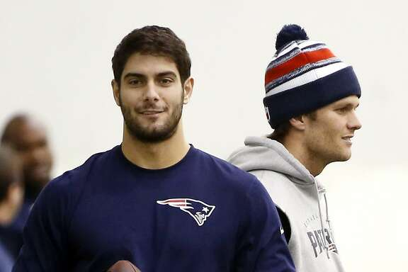 FILE- In this Feb. 1, 2015, file photo, New England Patriots backup quarterback Jimmy Garoppolo, left, holds a football as starting quarterback Tom Brady, right, stands by during a walkthrough at the NFL football team's facility in Foxborough, Mass. The NFL suspended Brady for the first four games on Monday, May 11, 2015, for his role in a scheme to deflate footballs used in the AFC title game. (AP Photo/Elise Amendola, File)