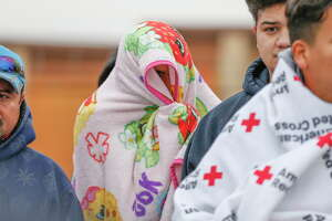 Victims of a fire destroyed an apartment complex at Allen-Genoa Road and Avenue H use blankets  to stay warm Tuesday, Dec. 26, 2017, in Houston. The Red Cross arrived to the scene at 8 a.m. to provide residents with food and blankets and were arranging to take them to a temporary shelter. Harris County Fire Marshall, Capt., Mitchell R. Weston, said that two firefighters were injured while battling the early morning blaze blaze.