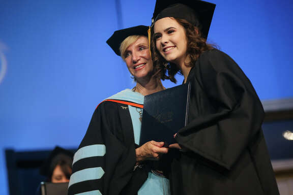 Graduate Kaitlyn McKenzie pauses for a photo with Lone Star College-Montgomery President Rebecca Riley after receiving her diploma during the Lone Star College-Montgomery commencement ceremony on Friday, May 12, 2017, at Woodlands Church. McKenzie is part of the first graduating class of iSchool High, a public charter school located on the LSC-Montgomery campus, and is one of three students graduating with their associates degrees before their high school degrees.