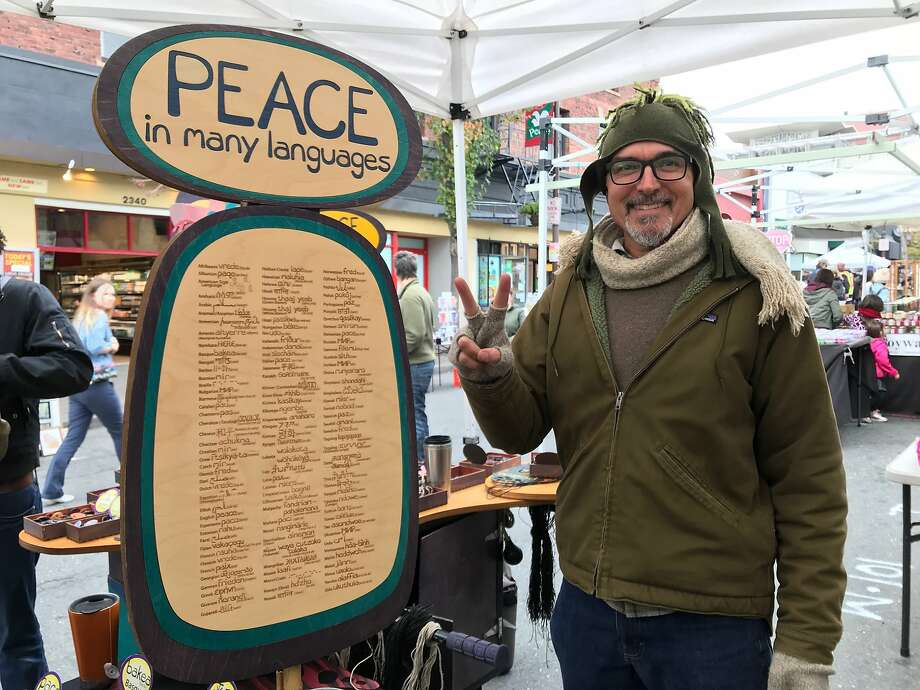 """Joe Murphy sells his pendants with the word for """"peace"""" in 123 languages. Photo: Beth Spotswood"""