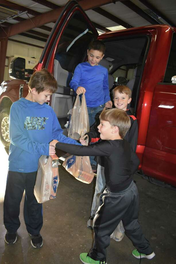The annual Needville Harvest Fest Food and Toy Drive was held in early December week, with donations pouring in to help those in the community. Clockwise, from left, are 10-year-old volunteer Cade Leopold accepting donations from 9-year-olds Logan Teykl and Layton Reed, and 6-year-old Weston Reed. Photo: Beverlie Pollock