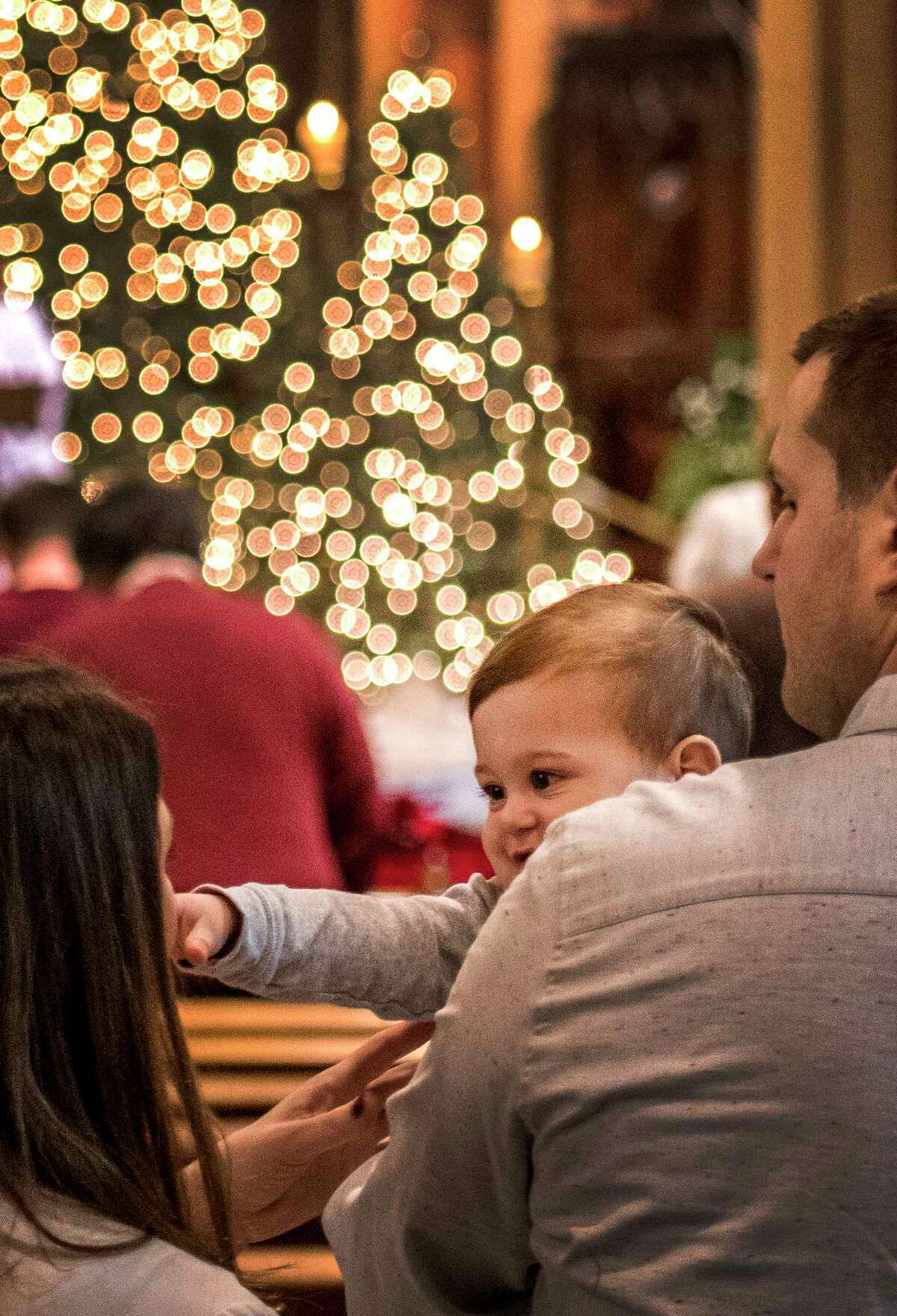 Mason Karasavov 11 months in the arms of his father Maksim Karasavov enjoys the beautiful music as he reaches out for his mom Amanda Ciotto during the Christmas Day service at the Cathedral of Immaculate Conception Monday Dec 25, 2017 in Albany, N.Y. (Skip Dickstein/ Times Union)