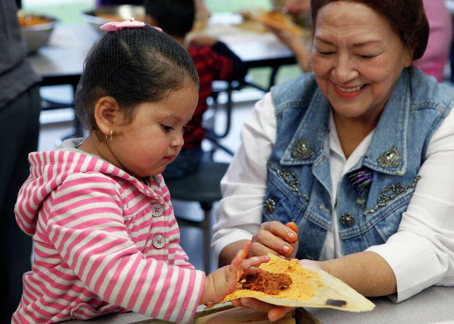 In this photo: Angelise Altamirano, 2, learns how to make tamales from Virginia Casas. Photo: Cynthia Esparza, For The San Antonio Express-News / ©2014 San Antonio Express-News