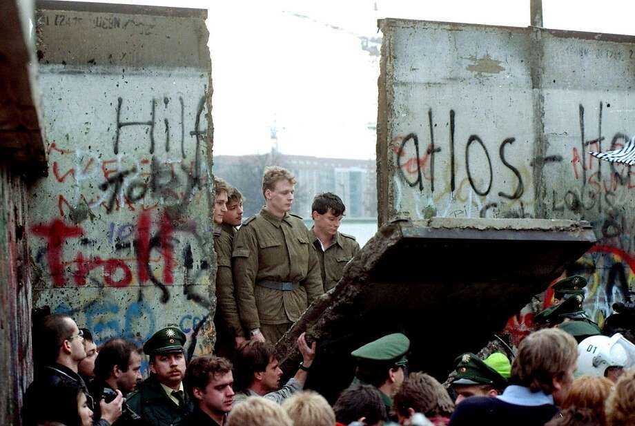 East German border guards watch as demonstrators pull down a segment of the Berlin Wall in 1989. A nursing home tries to trigger such memories as a form of therapy for dementia. Photo: LIONEL CIRONNEAU, Associated Press