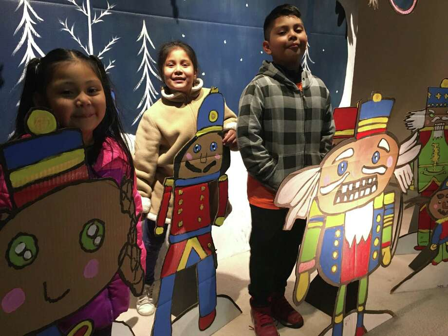 Students from the Connecticut Academy of Fine Art in Torrington created a holiday art bomb downtown, using the window of the former Libby's Furniture store. From left are Yarelie, 5, Zalisha, 7 andNick, 9 with their nutcrackers. Photo: Photo By Teresa Graham-Sullivan