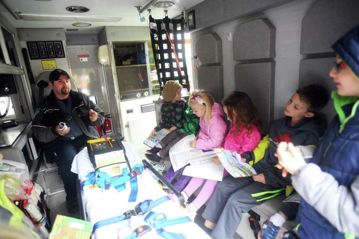 A group of kids listen to Stamford EMT Steve Gill describe the tools inside an ambulance during a Touch a Truck event at the Stamford Museum and Nature Center in November.