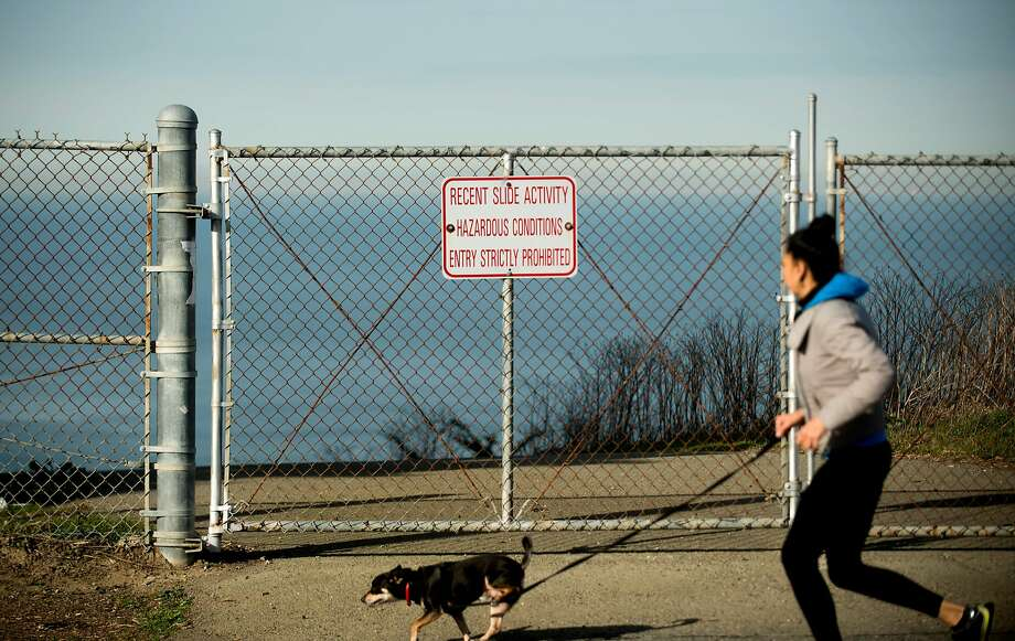 A jogger passes a warning sign on Avalon Drive in Daly City near an eroding cliffside high above the Pacific Ocean. Photo: Noah Berger, Special To The Chronicle