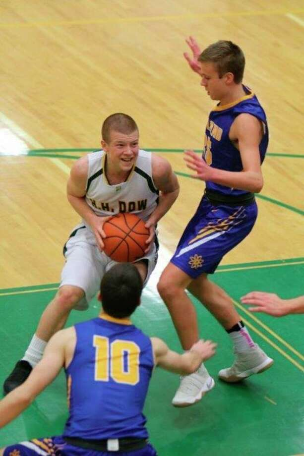 Former Dow High star point guard Trevor Davis (left) is seen here in a game against Midland High during the 2016-17 season. Davis recently transferred from Adrian College to play basketball for Northwood University. (photo provided)