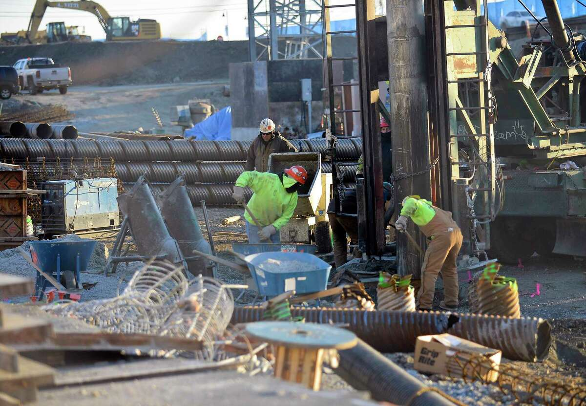 Construction workers bundle up from the bitter cold weather as they set pilings for new construction at Harbor Point in Stamford, Conn. on Tuesday, Dec. 26, 2017.