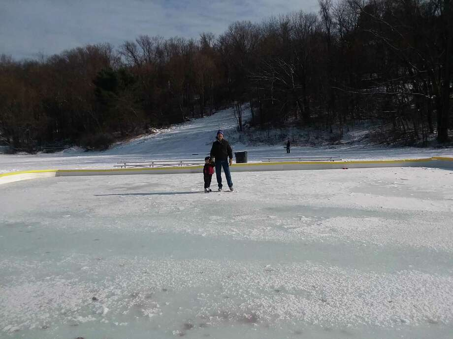 An Ansonia father and his son test out the public skating rink installed in Linett Park. The sledding hill is in the background. Photo: / Contributed Photo