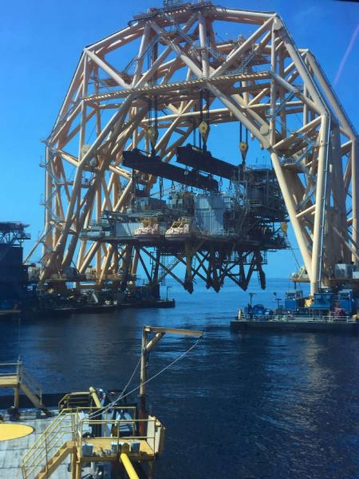 Cranes on a heavy lift vessel remove the topsides of Shell's 36-year-old Cougar oil and gas platform.