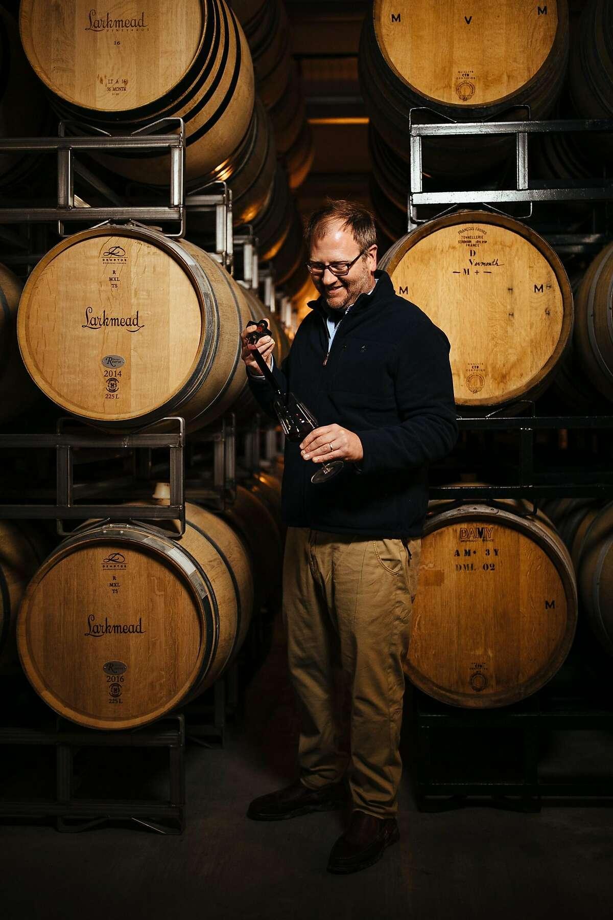 Dan Petroski uses a wine thief to taste wines from barrel at Larkmead Vineyards.