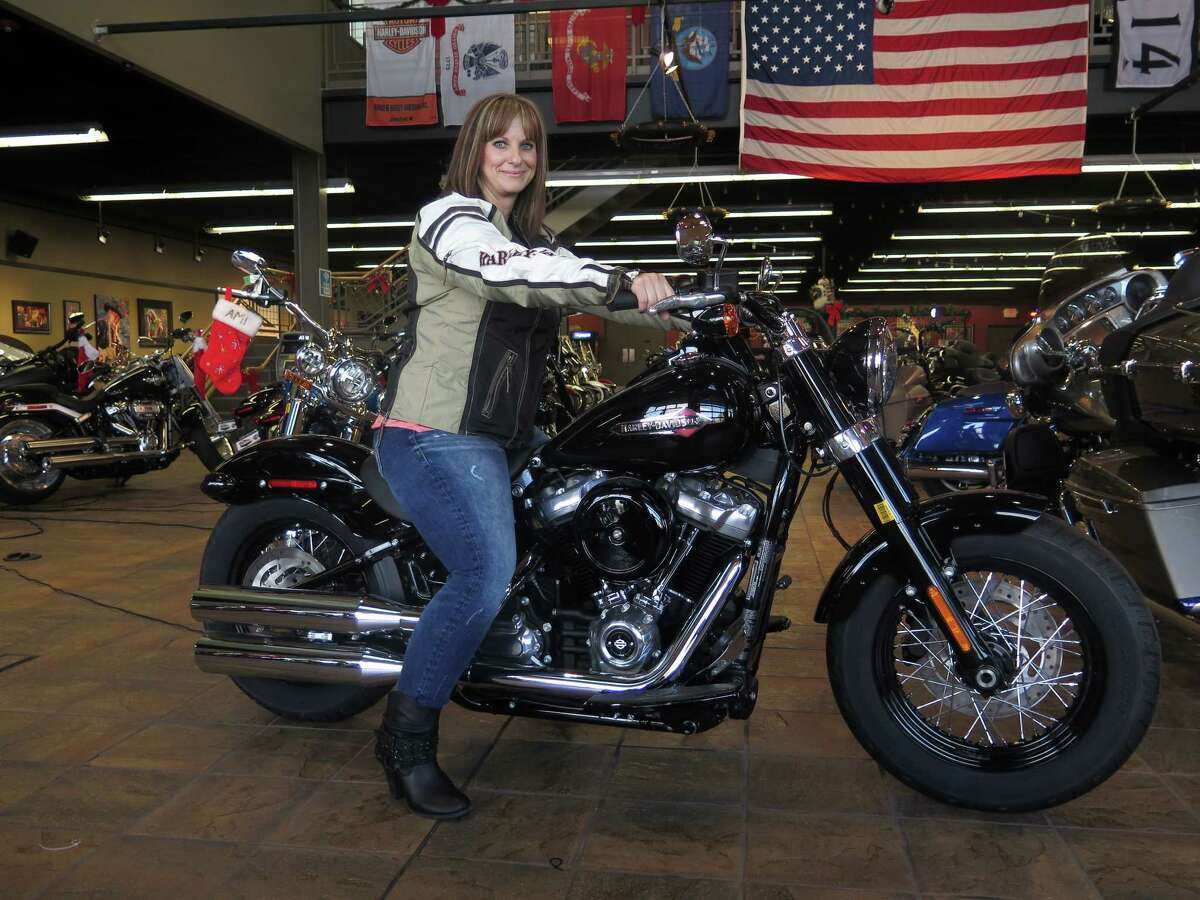 In this Dec. 12, 2017, photo, Terri Meehan poses on a 2018 Harley Softail Slim in Milwaukee's House of Harley. Meehan took a riding course at the dealership as part of Harley-Davidson's