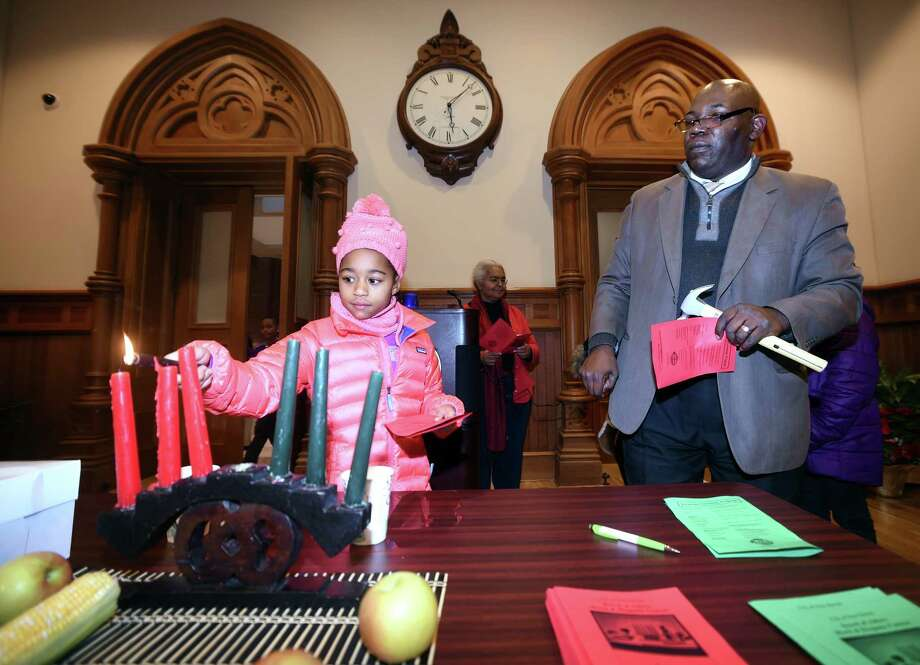 Nia Jackson, 8, of New Haven lights the second candle for Kwanzaa after reciting the principal of Kujichagulia, Self-Determination, during the Annual Kwanzaa Ceremony hosted by the Board of Alders Black & Hispanic Caucus at City Hall in New Haven on December 26, 2017.  At right is Al Lucas, Director of Legislative Services. Photo: Arnold Gold, Hearst Connecticut Media / New Haven Register