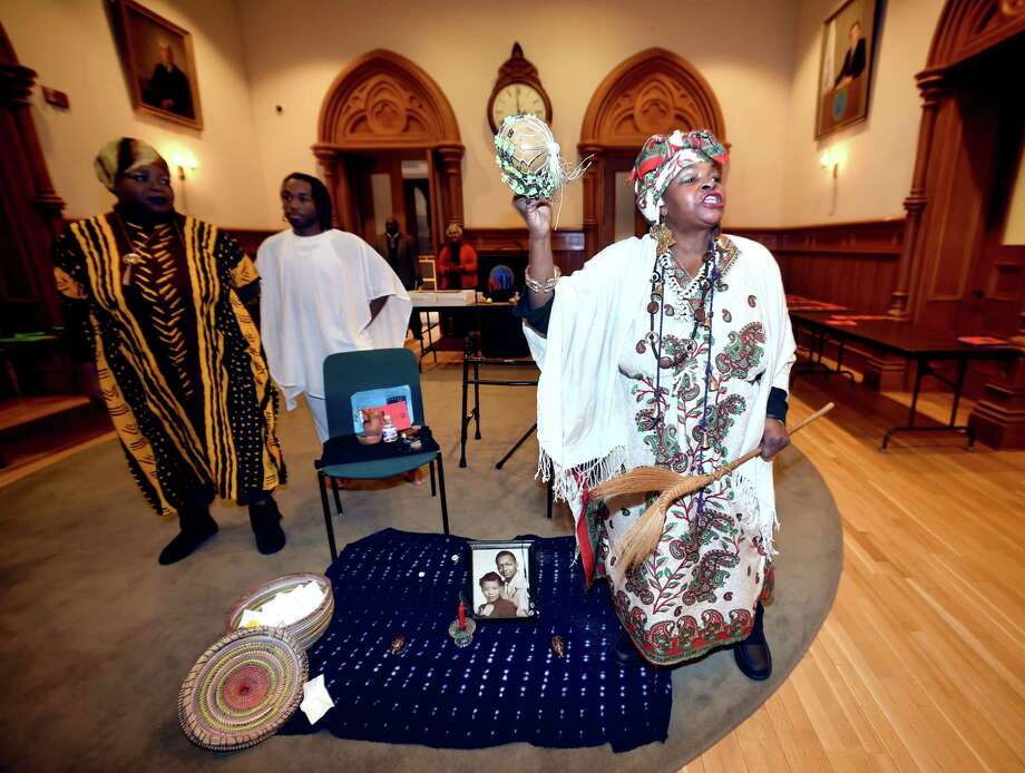 Elaine Peters (right) performs a Call to Ancestors to begin the Annual Kwanzaa Ceremony hosted by the Board of Alders Black & Hispanic Caucus at City Hall in New Haven on December 26, 2017.  Assisting Peters was Marcey Jones (left) and Earl Ali-Randall (center). Photo: Arnold Gold, Hearst Connecticut Media / New Haven Register