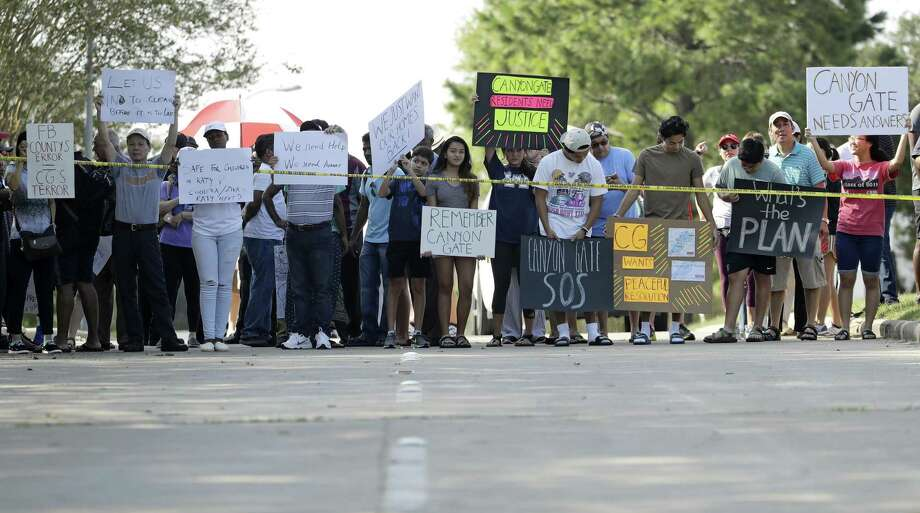Residents hold signs at a roadblock into their Canyon Gate neighborhood which was flooded when the Barker Reservoir reached capacity in the aftermath of Harvey Saturday, Sept. 2, 2017, in Katy, Texas. Residents gathered at the checkpoint to vent their frustrations about not being able to get back into their homes which will remain flooded for several more days while the reservoir drains. (AP Photo/Charlie Riedel) Photo: Charlie Riedel, STF / Associated Press / Copyright 2017 The Associated Press. All rights reserved.