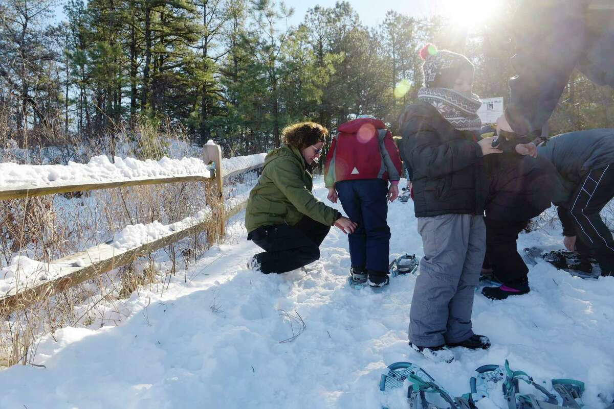 Jackie Citriniti, lead educator for the Albany Pine Bush Preserve, helps people get into their snowshoes for the 9th Annual Cookie Burner Stroll on Tuesday, Dec. 26, 2017, in Albany, N.Y. On Wednesday at 10:00am, the Discovery Center at the Pine Bush will hold their Scoop on Poop event, to learn about animal scat and what it can tell you about the animal. Participants will also use Play-Doh to make animal scat. Starting on Wednesday at 1:00pm and running through Friday, for children 10 years of age and older, the center will hold their Karner Kids Film Festival where children will work on ideas and learn to make their own film about the Pine Bush. Registration is required for the film festival. (Paul Buckowski / Times Union)