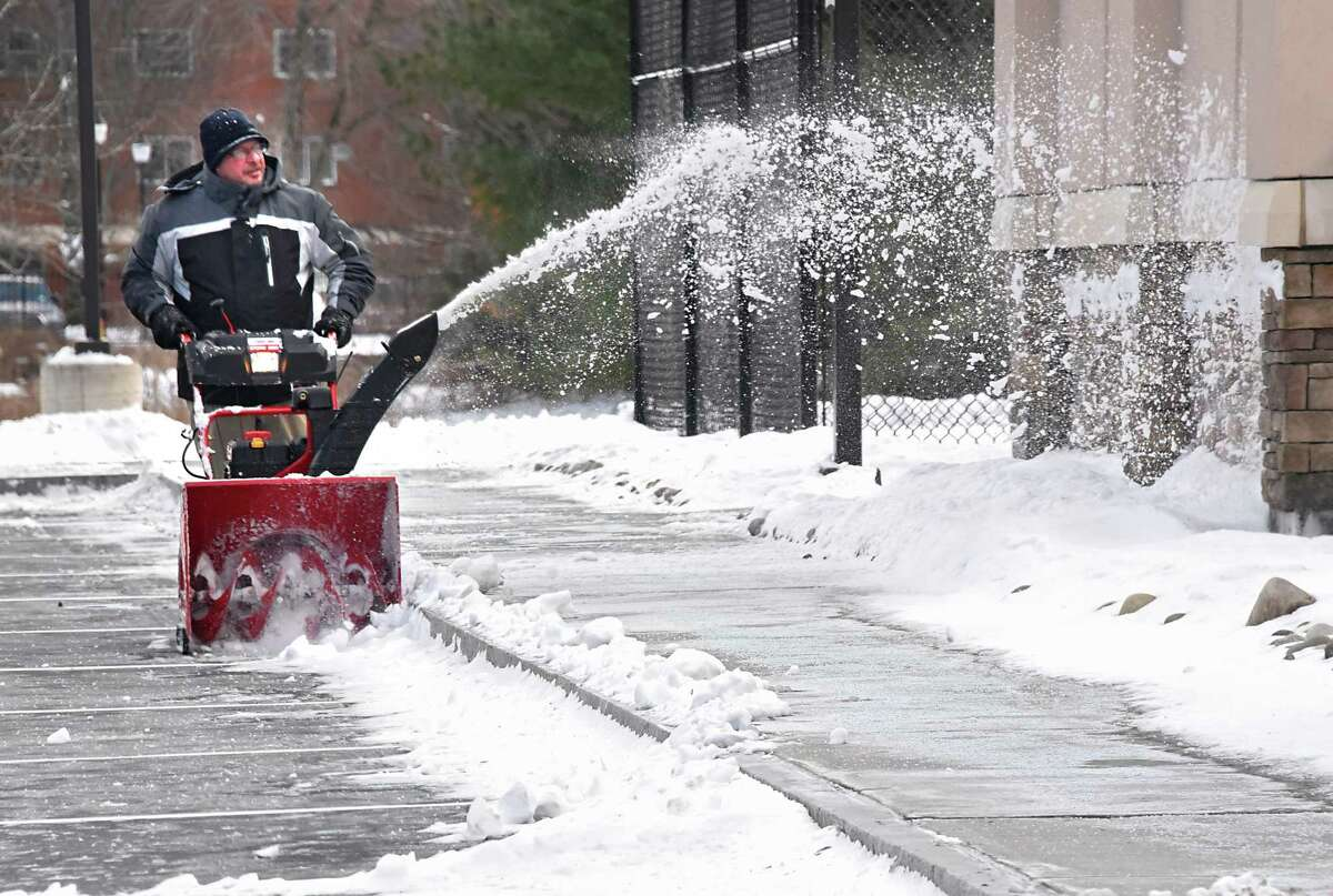 A man clears snow from a hotel parking lot and sidewalk with a snowblower on Tuesday, Dec. 26, 2017 in Colonie, N.Y. (Lori Van Buren / Times Union)